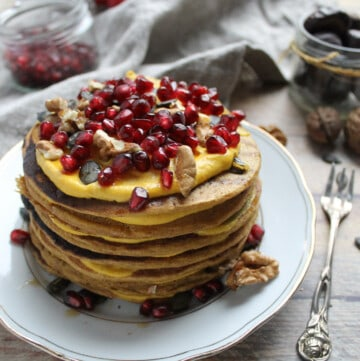 pile of pumpkin pancakes topped with pumpkin cream and pomegranate
