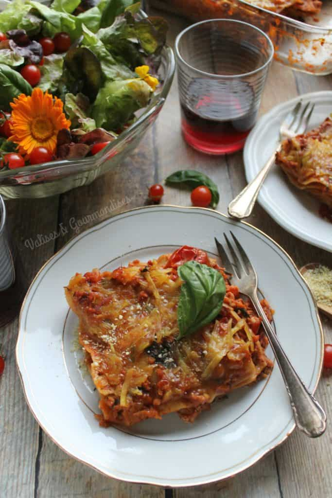 Vegan bolognaise lasagna on a table with red wine