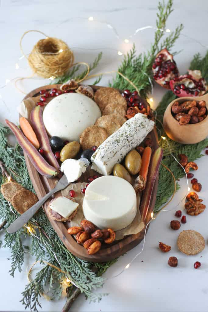 cheese platter on pine branches with fairy lights
