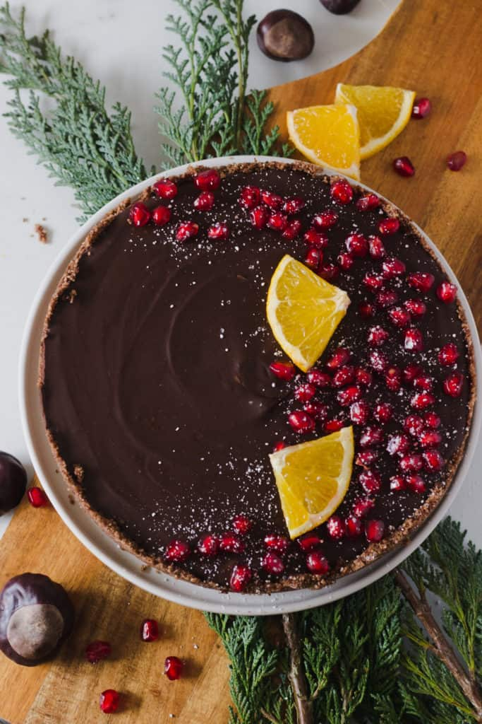 chocolate tart seen from above, topped with pomegranate and orange slices