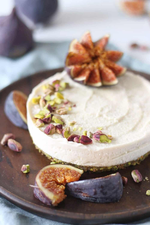 Gâteau au fromage fermenté végane avec figues fraîches et pistaches dans une assiette en bois