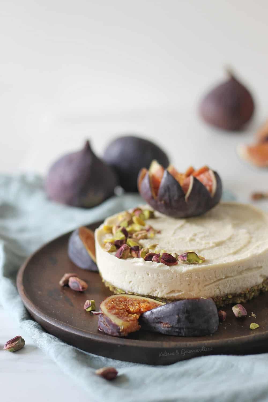 cheesecake vegan fermenté garni de figues fraîches et de pistaches dans une assiette en bois