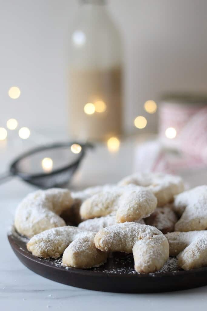 crescent cookies on a plate with twinkle lights in background