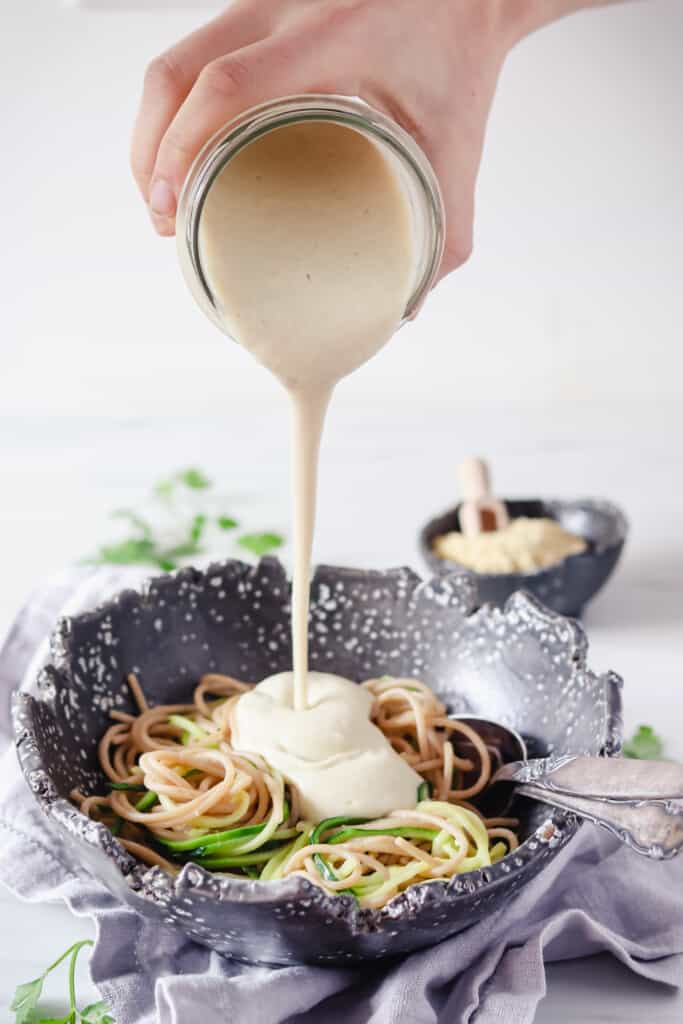 Oil-free Alfredo sauce being poured on pasta