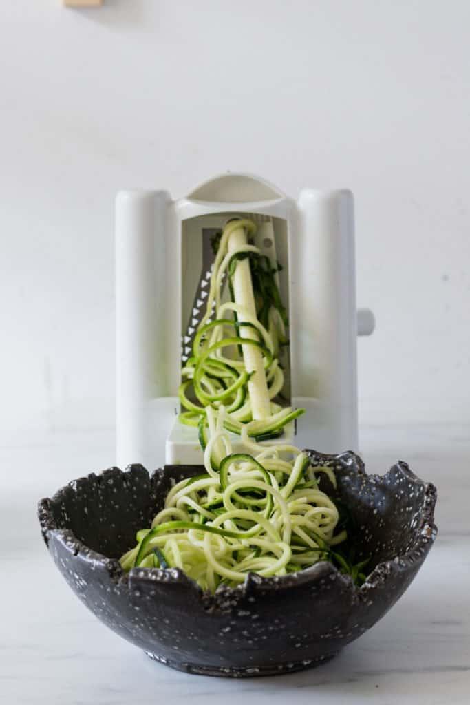 zucchinouilles qui sortent du spiraliseur et tombent dans un bol noir