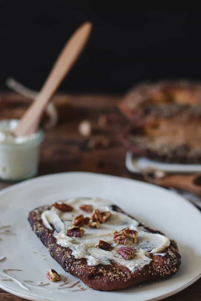 pumpkin beaver tail on a plate with cream cheese frosting and chopped pecans