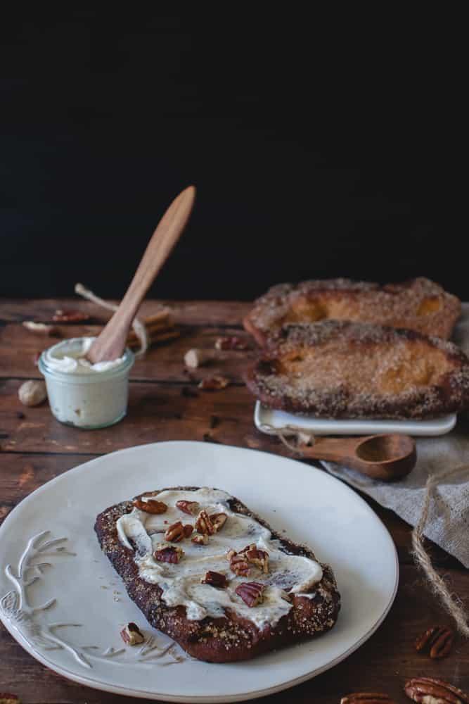 queue de castor à la citrouille garnie de glaçage au fromage à la crème végane et pacanes dans une assiette