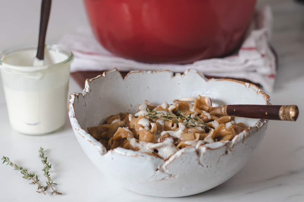 mushroom stroganoff in bowl topped with vegan cream and fresh thyme
