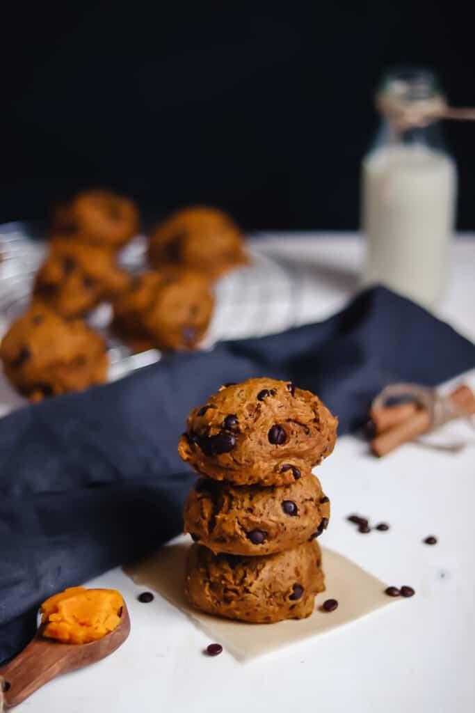 3 biscuits à la citrouille empilés avec bouteille de lait d'avoine et plus de biscuits en arrière-plan