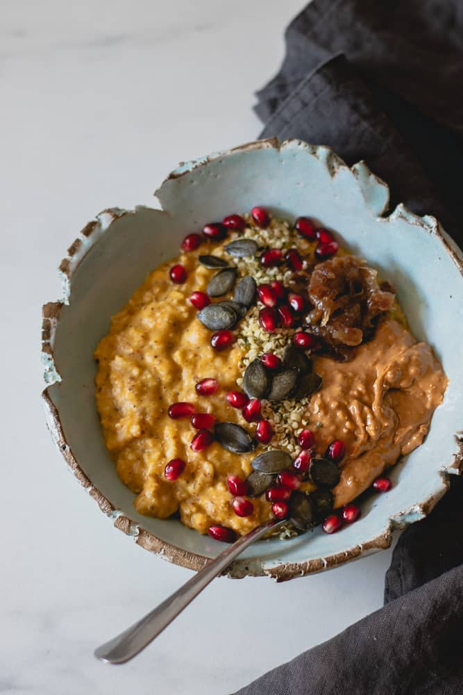 pumpkin oatmeal in blue bowl seen from above, topped with date caramel, cashew butter, pumpkin & hemp seeds and pomegranate